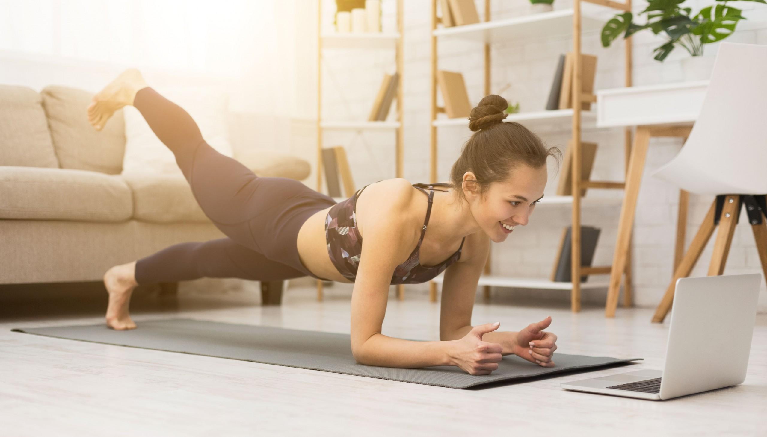 Frau macht Liegestuetz vorm Laptop