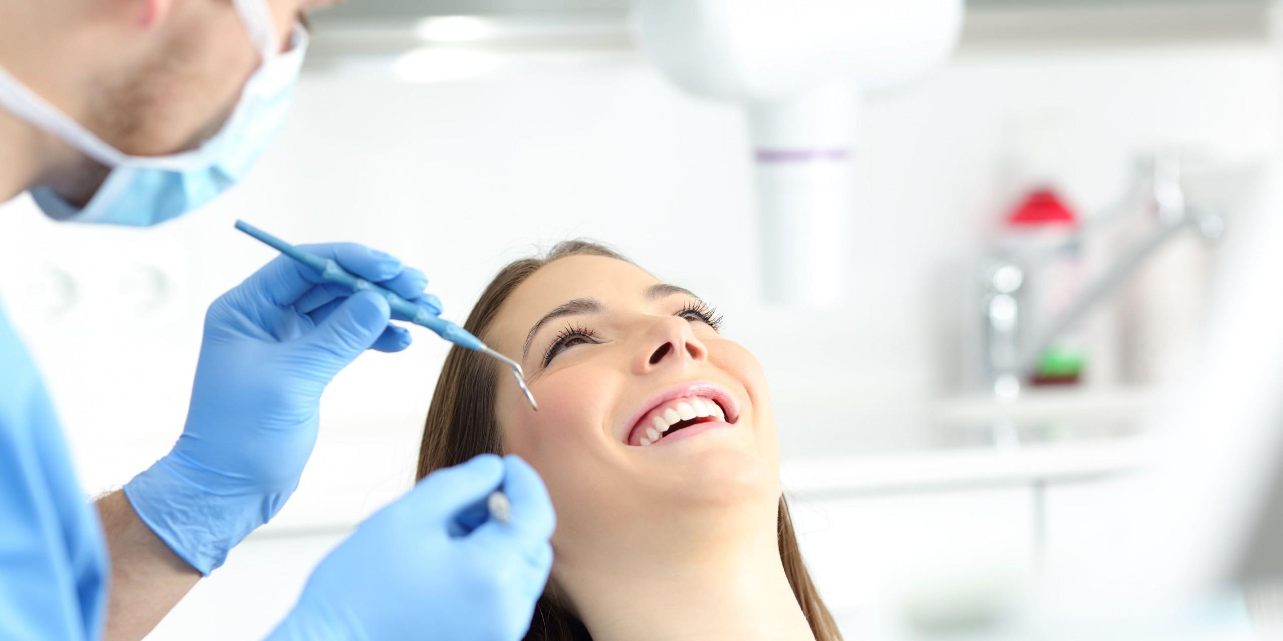 Frau sitzt lächelnd auf dem Zahnarztstuhl und wartet, dass der Zahnarzt mit der Zahnreinigung beginnt.