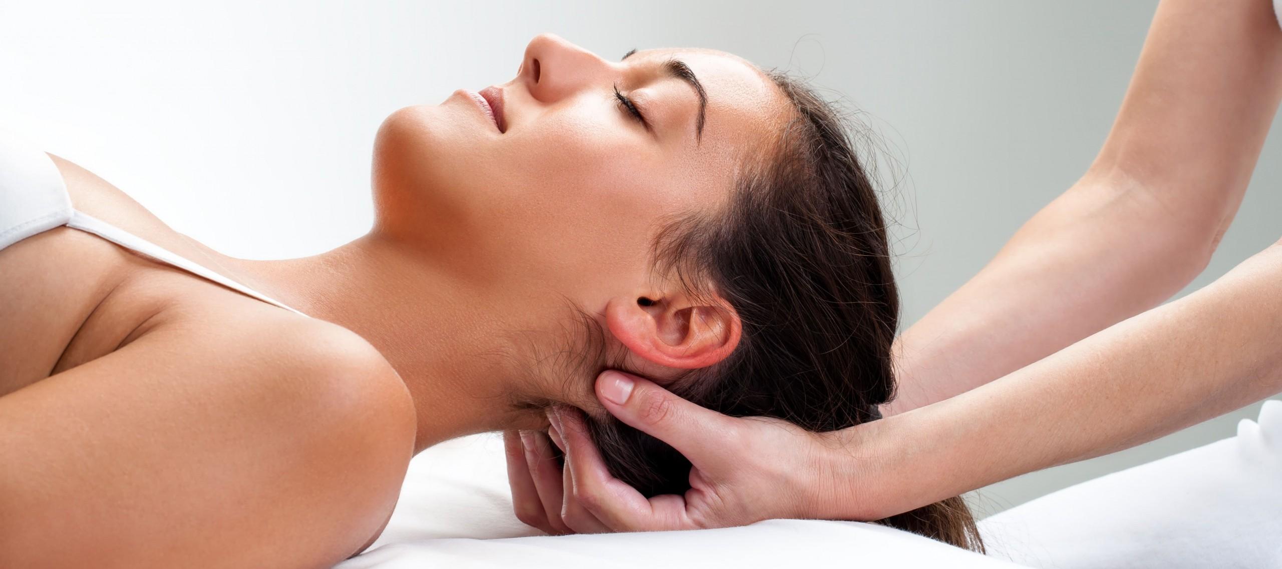 Frau liegt entspannt mit dem Rücken auf einer Liege und wird von einer Osteopathin am Nacken behandelt.