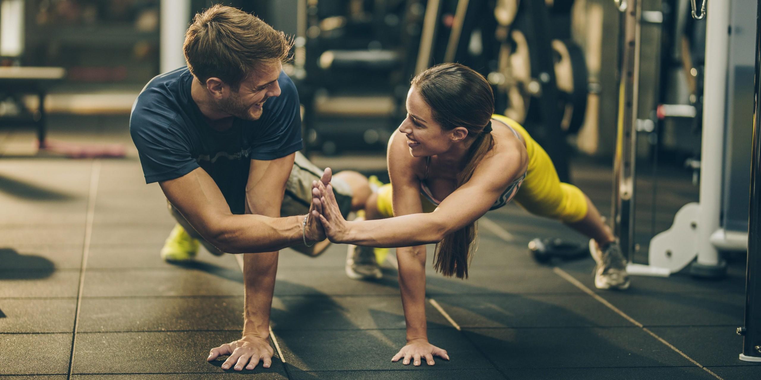 Mann und Frau im Fitnessstudio klatschen sich im Liegestütz die Hände ab.