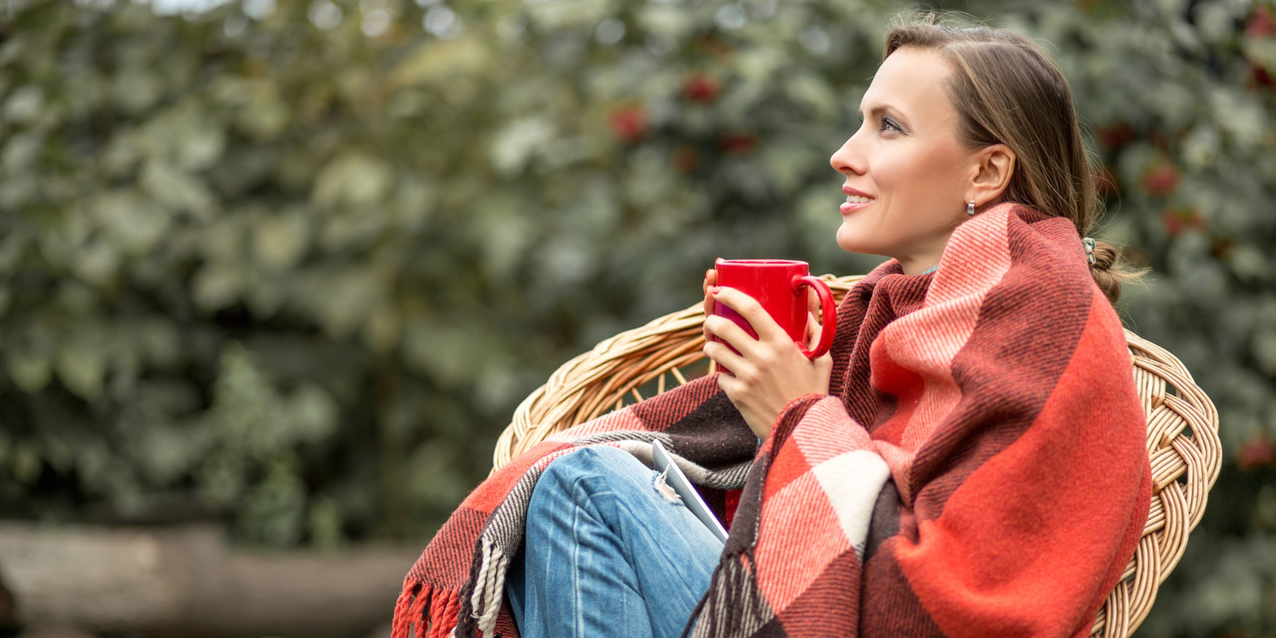 Frau sitzt draußen auf einem Rattanstuhl, eingehüllt in eine Decke, mit einer roten Tasse in beiden Händen.