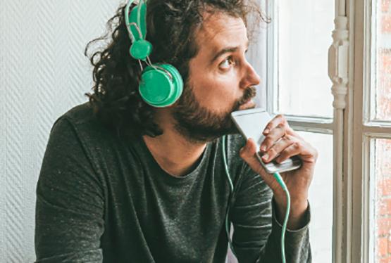 junger Mann mit Kopfhöhrern schaut nachdenklich aus dem Fenster
