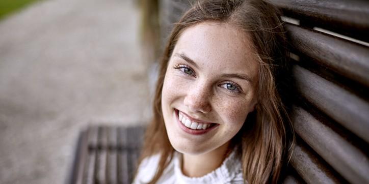 Frau sitzt auf einer Holzbank und schaut lächelnd in die Kamera.