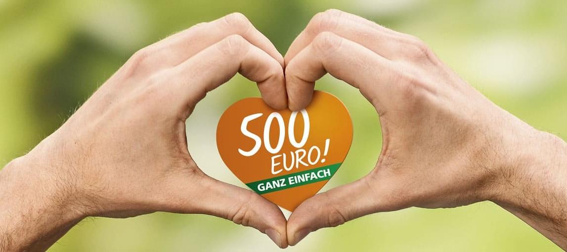 Zwei Hände formen ein Herz um ein herzförmiges Papier mit dem 500 Euro Logo darauf.
