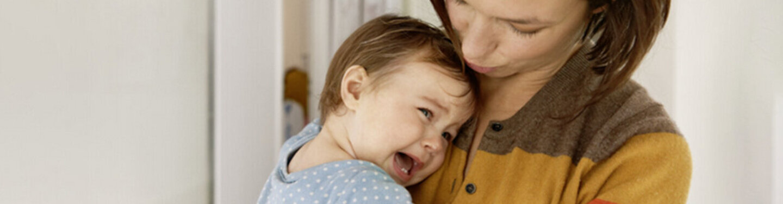 Baby schreit bei Mutter auf dem Arm