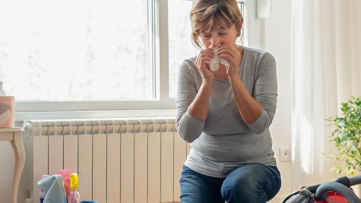 Eine Frau schnäubt sich die Nase wegen einer Hausstaubmilbenallergie.