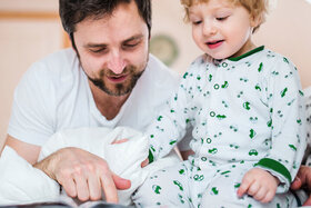 Vater liegt neben seinem Sohn, gemeinsam wird ein Buch angeschaut.