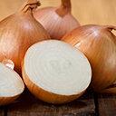 Halbierte Zwiebel und mehrere ungeschälte Zwiebeln