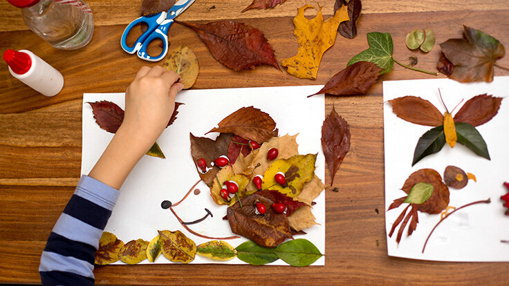 Kind bastelt Igel aus Blättern.