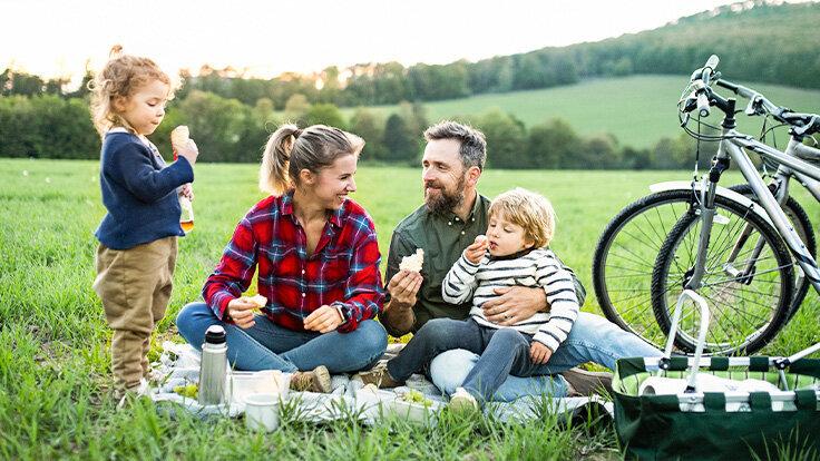 Eine Familie mit zwei Kindern macht eine Picknick-Pause bei ihrer Radtour.