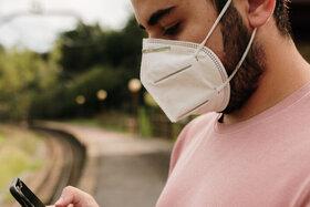 Junger Mann trägt FFP2-Maske und steht am Bahnhof.