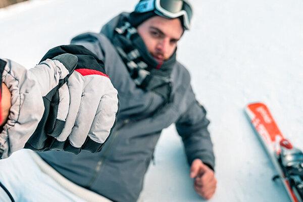 Jungem Mann wird nach einem Unfall beim Wintersport aufgeholfen.