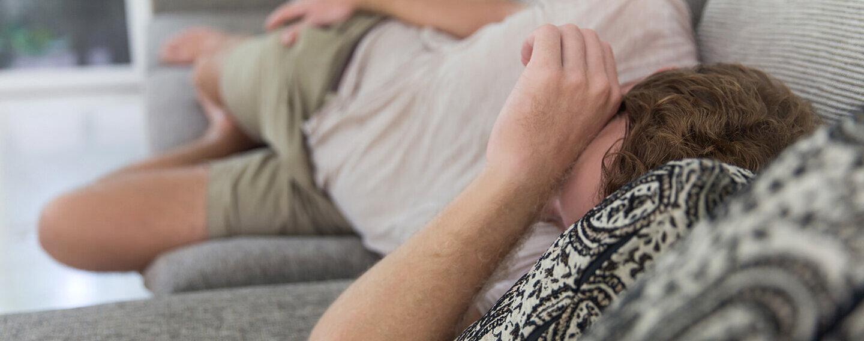 Ein Mann liegt erschöpft und mit Schmerzen auf der Couch.