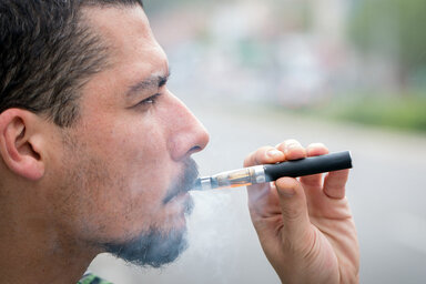 Ein junger Mann raucht eine E-Zigarette.