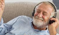 Ein älterer Herr genießt Musik hören über Kopfhörer