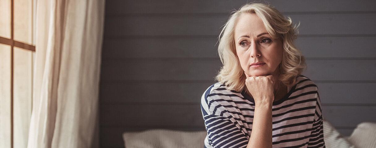 Eine Frau, die unter chronischen Schmerzen leidet, sitzt mit traurigem Blick auf dem Sofa.