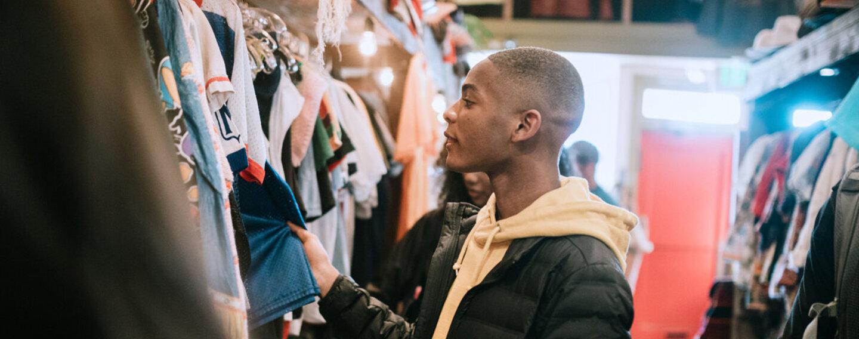 Ein junger Mann stöbert durch nachhaltige Kleidung.