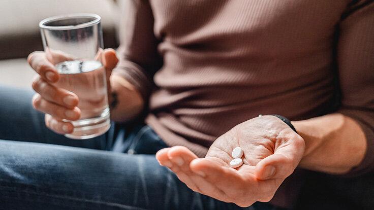 Mann nimmt Medikamente gegen Genitalherpes.