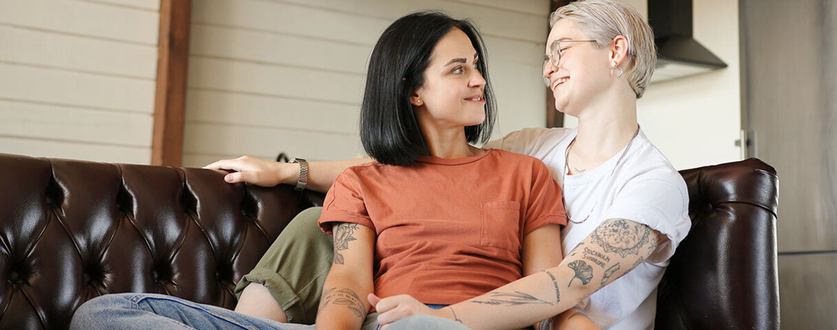 Junges Paar liegt zufrieden auf dem Sofa, weil die Kommunikation in der Beziehung stimmt.
