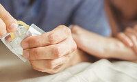 Ein Mann und eine Frau öffnen eine Kondompackung, sie praktizieren Safer Sex.