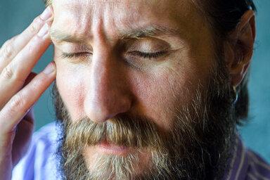 Mann greift sich an die Schläfe, er leidet unter einseitigen Kopfschmerzen, Clusterkopfschmerzen genannt.