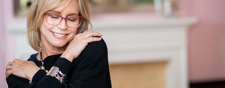 Eine ältere Frau umarmt sich selbst.