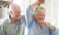Älteres Paar tanzt lächelnd in der Küche