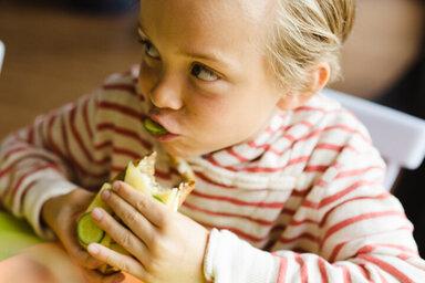 Kind isst Brot mit Gurken, denn eine gesunde Ernährung verhindert Übergewicht.