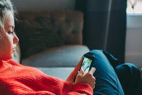 Ein junges Mädchen in einem roten Pullover schaut auf ihr Smartphone.