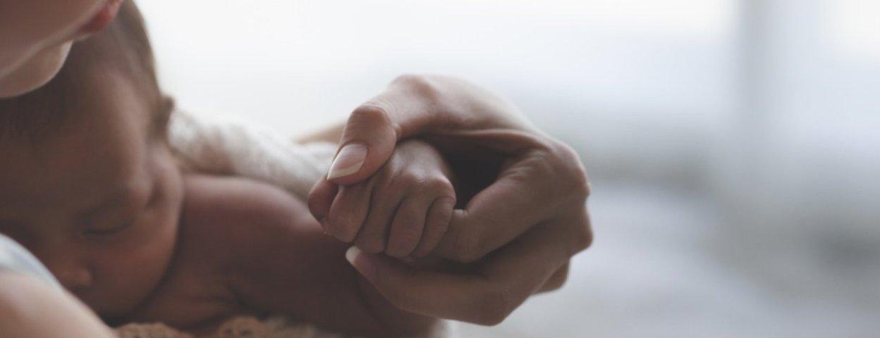 Mutter hält Neugeborenes im Arm.