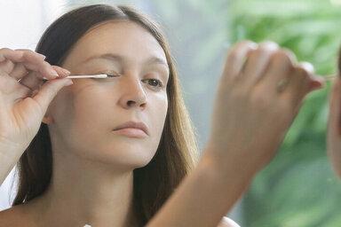 Eine Frau benutzt vor dem Spiegel Wimperntusche