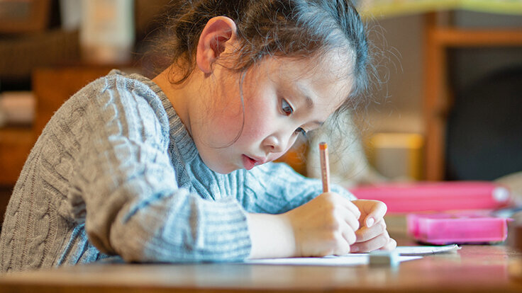 Ein Mädchen lernt und schreibt mit Handschrift.