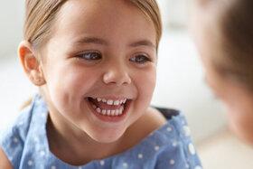 Lachendes Mädchen wird von Ärztin untersucht.