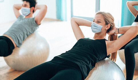Frau und Mann machen Sport mit Mundschutz.