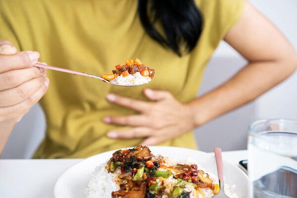 Eine Frau hat Magenschmerzen beim Essen und hält sich die Hand vor den Bauch.
