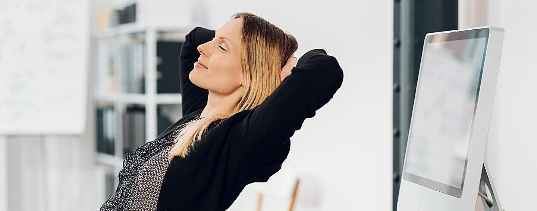 Eine junge Frau nimmt sich einen Moment Zeit, um sich am Schreibtisch zu entspannen.