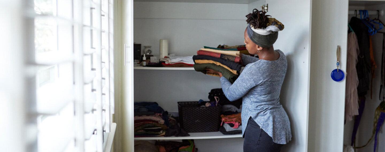 Frau räumt Kleiderschrank aus.