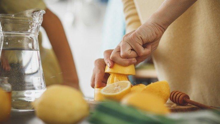 Frau presst Zitronen zur Saftherstellung aus