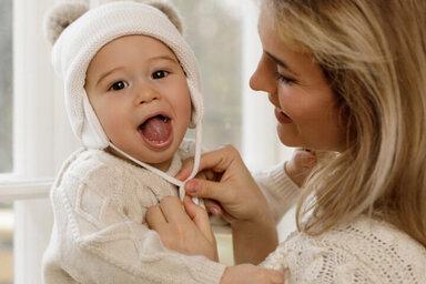 Babys richtig anziehen - Mutter setzt ihrem Kind eine Mütze auf.