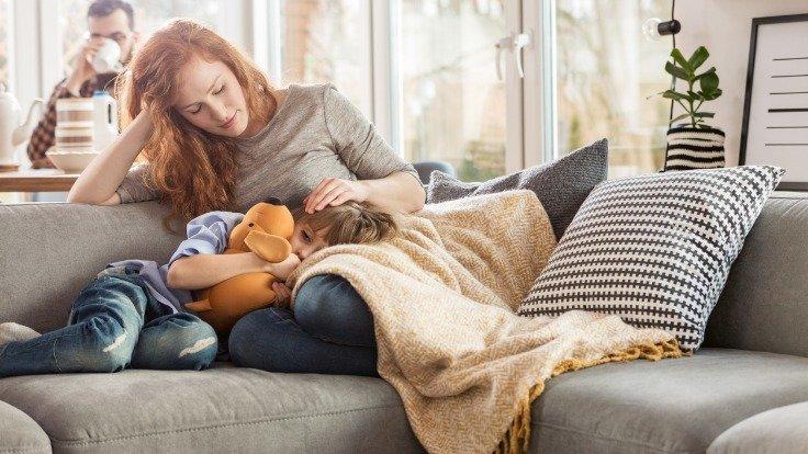 Junge Frau liegt mit erkranktem Kind auf dem Sofa.