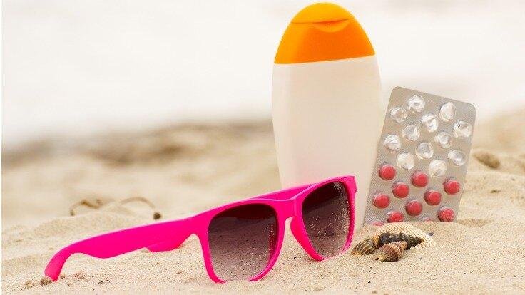 Sonnenbrille, Sonnenmilch und Arzneimittel liegen im Sandstrand