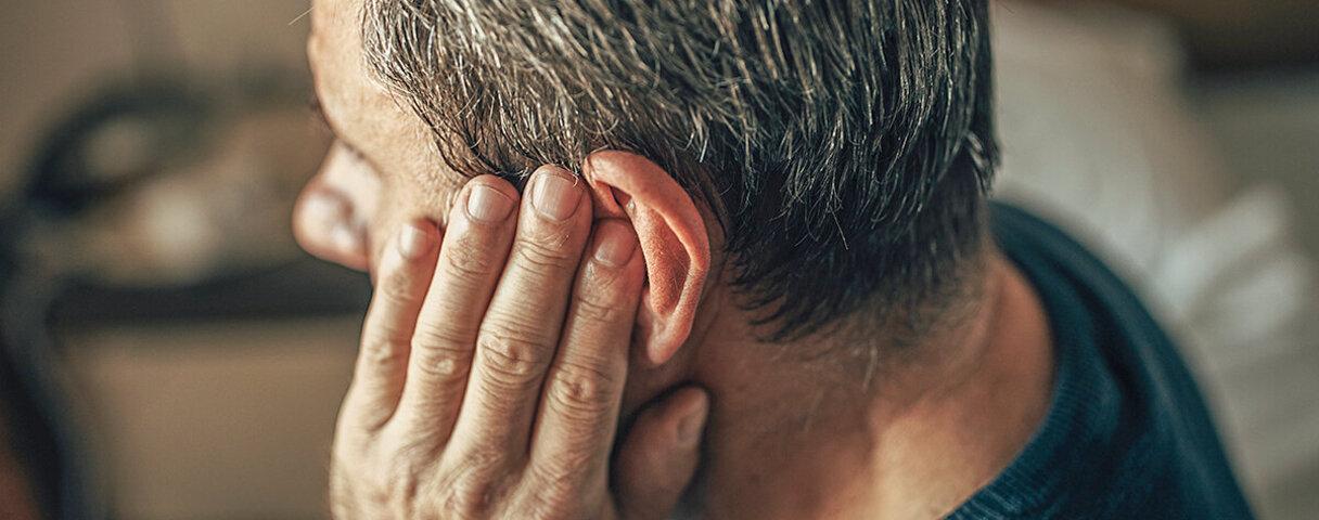 Mann hält sich das Ohr, weil er einen Tinnitus hat.
