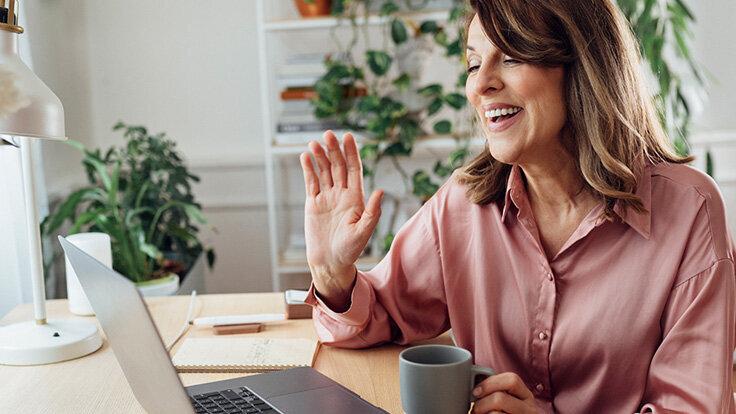 Eine Frau begrüßt ihre Kollegen im Videotelefonat am Laptop aus dem Homeoffice.