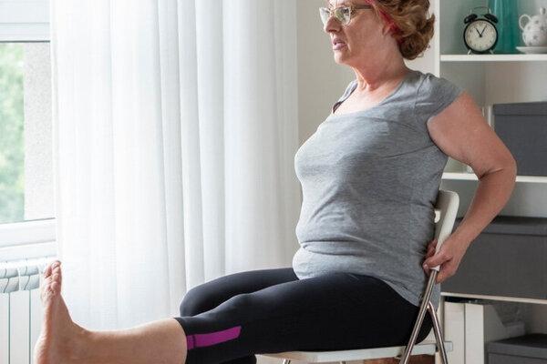 Seniorin bei einer Beweglichkeitsübung auf einem Stuhl im Wohnzimmer.