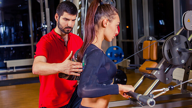 Frau bleibt in Bewegung und trainiert mit Fitnesstrainer an Geräten.