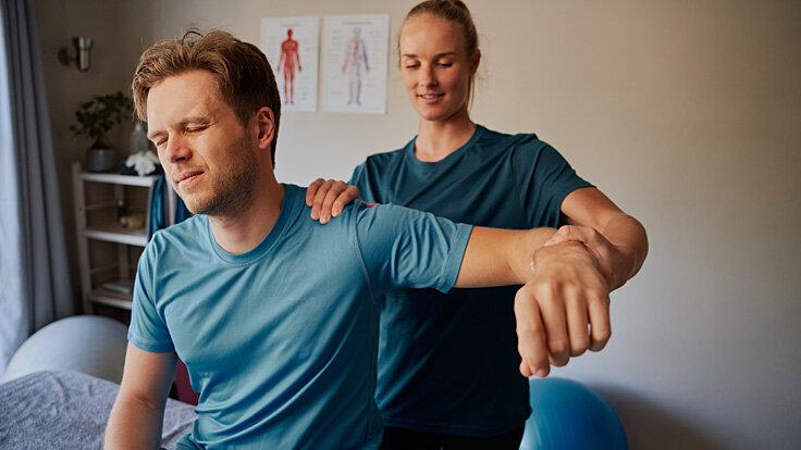 Ein junger Mann ist bei einer Physiotherapeutin, die ihm mit Krankengymnastik bei den Beschwerden in der Schulter hilft.
