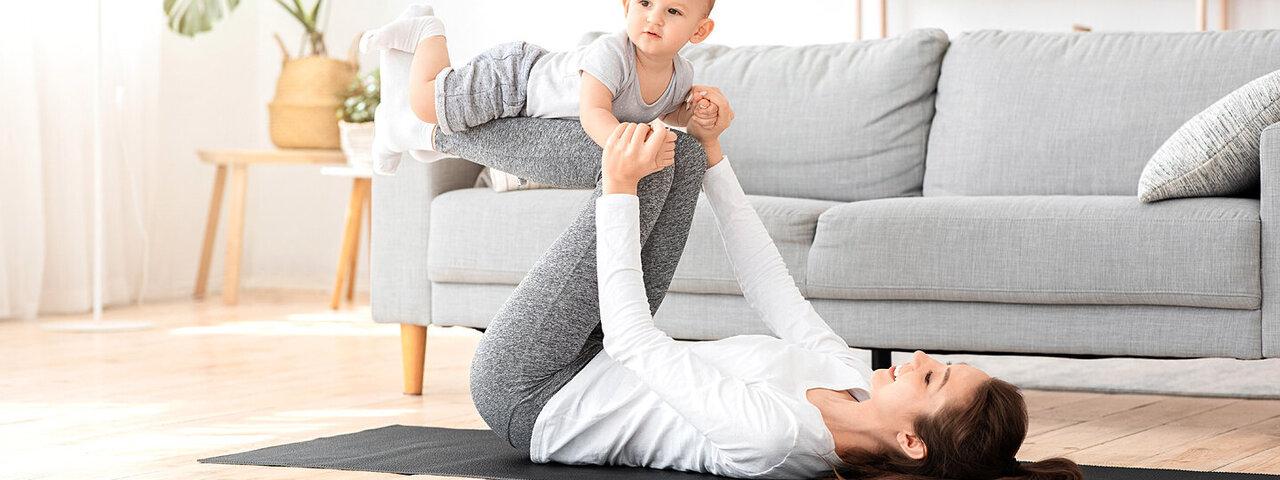 Eine junge Mutter macht Fitnessübungen und ihr Kind liegt auf ihren Beinen.