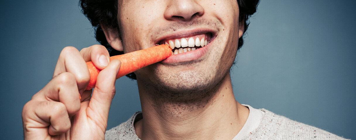 Ein junger Mann beißt von einer Karotte ab.