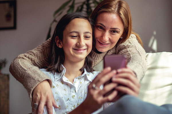 Eine Mutter schaut gemeinsam mit Ihrer Tochter etwas auf dem Smartphone an