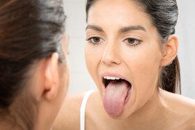 Frau checkt belegte Zunge im Spiegel